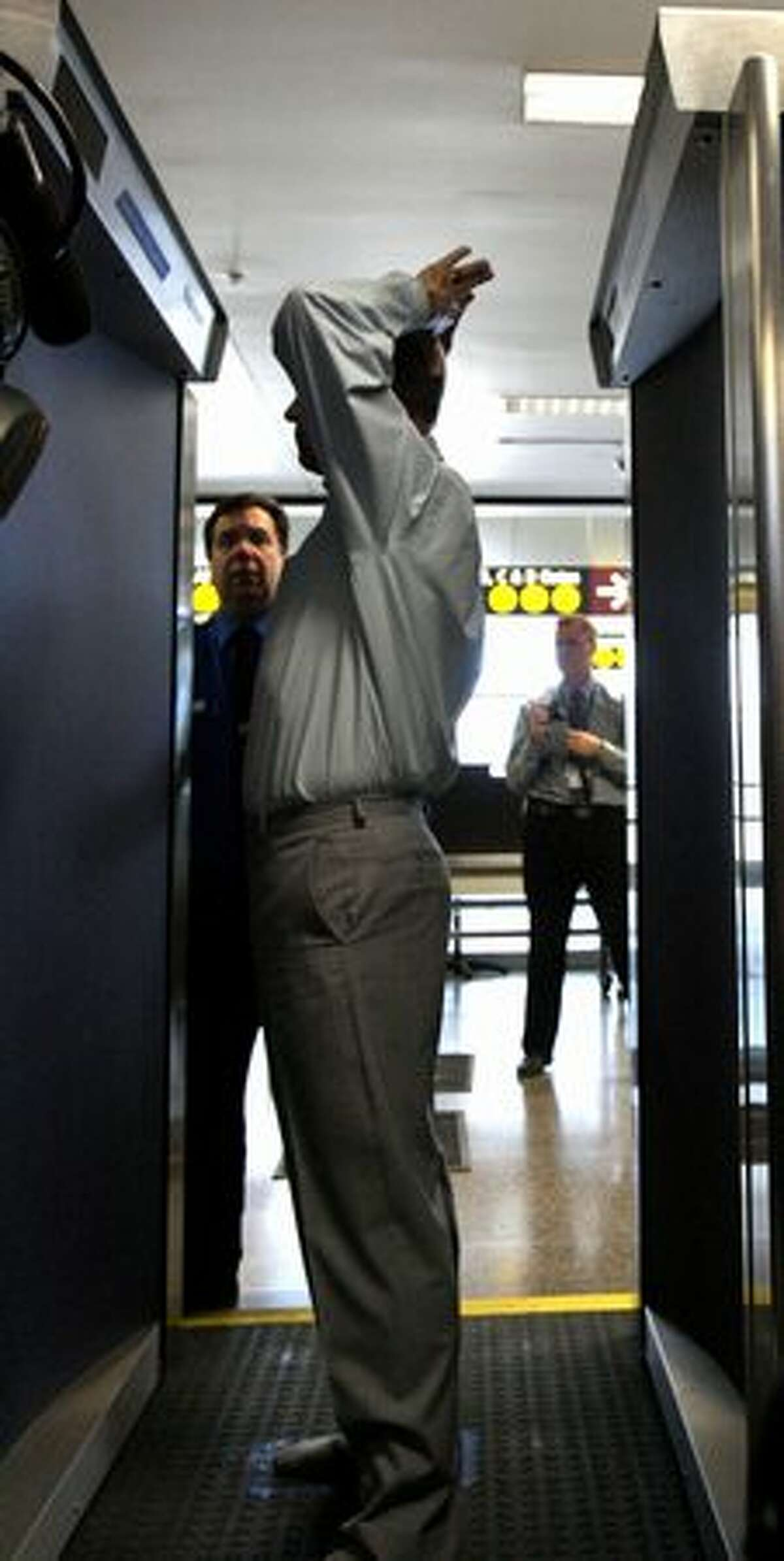 A Transportation Security Administration employee demonstrates a backscatter X-ray body scanner at Sea-Tac Airport.