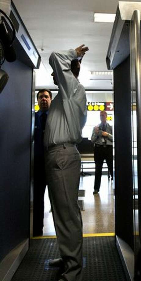 A Transportation Security Administration employee demonstrates a backscatter X-ray body scanner at Sea-Tac Airport. Photo: Aubrey Cohen, Seattlepi.com