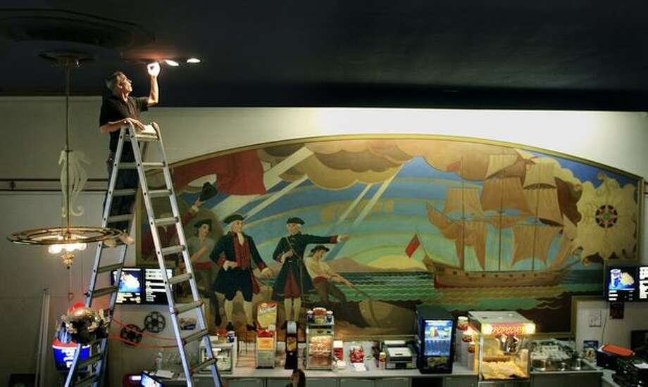 The October 2007 photo caption read: An early-1940's mural provides the backdrop to the concession stand as promotional manager Steve Garrett replaces ceiling lights in the lobby of the Admiral Theater. Photo: P-I File