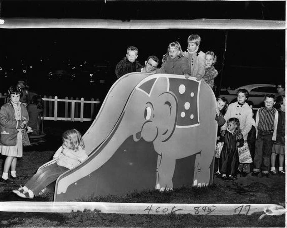 Kids playing on the elephant slide at the Kiddie Korral playground in front of the Aurora Drive-In Theater, Oct. 4, 1957. [NOTE: Marks were made by a former P-I photo editor.] Photo: P-I File