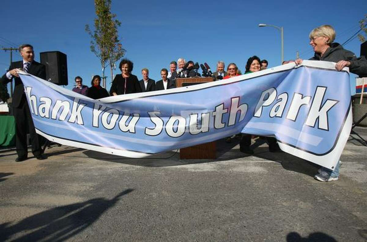 King County Executive Dow Constantine, left, and U.S. Senator Patty Murray unfurl a banner thanking the South Park community on Friday, October 15, 2010 after making an official announcement that funding has been secured to replace the closed South Park Bridge.