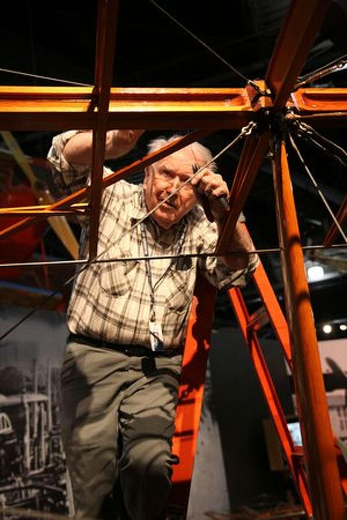 Museum volunteer Pete Graven adjusts turnbuckles on the wings of the Seattle Museum of Flight's Curtiss JN-4D Jenny.