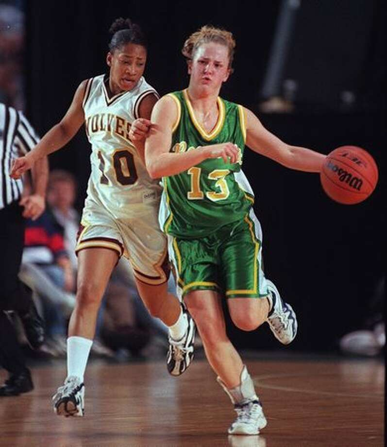 The March 1999 photo caption read: Roosevelt guard Lindsay Wilson (13) pushes the ball up the court with South Kitsap's Kristin Boyd on her hip. Photo: P-I File