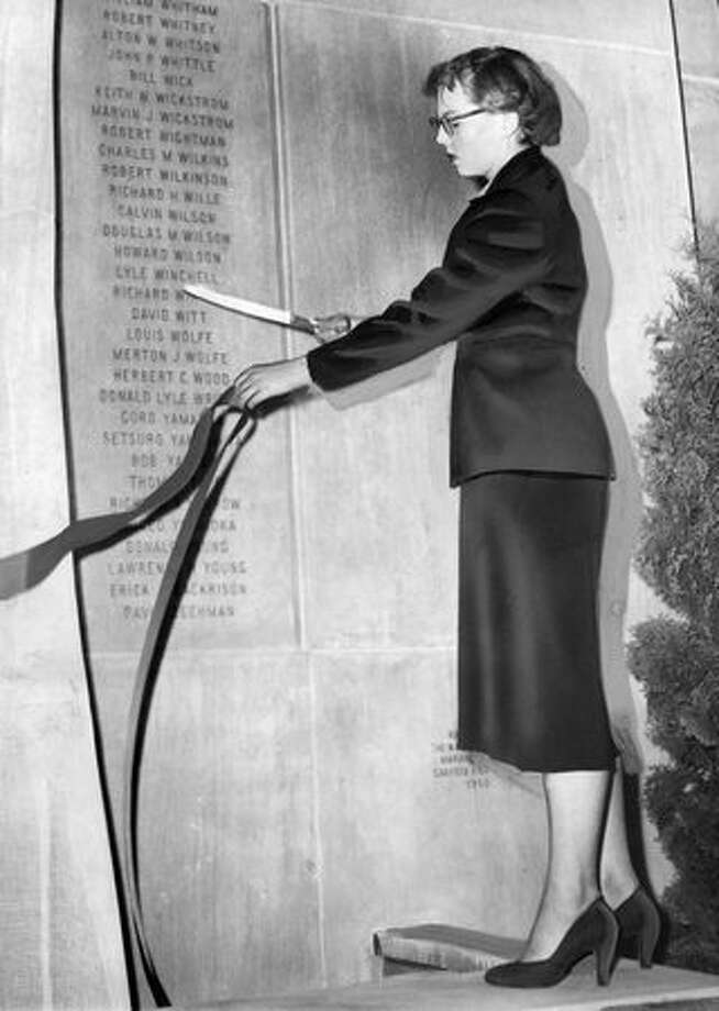 In this 1951 photo, Marianne Hanson, then a recent Garfield High graduate, cuts the ribbon that unveiled the shrine at Seattle High School Memorial Stadium honoring high school graduates who died in World War II. Hanson designed the shrine. Photo: P-I File
