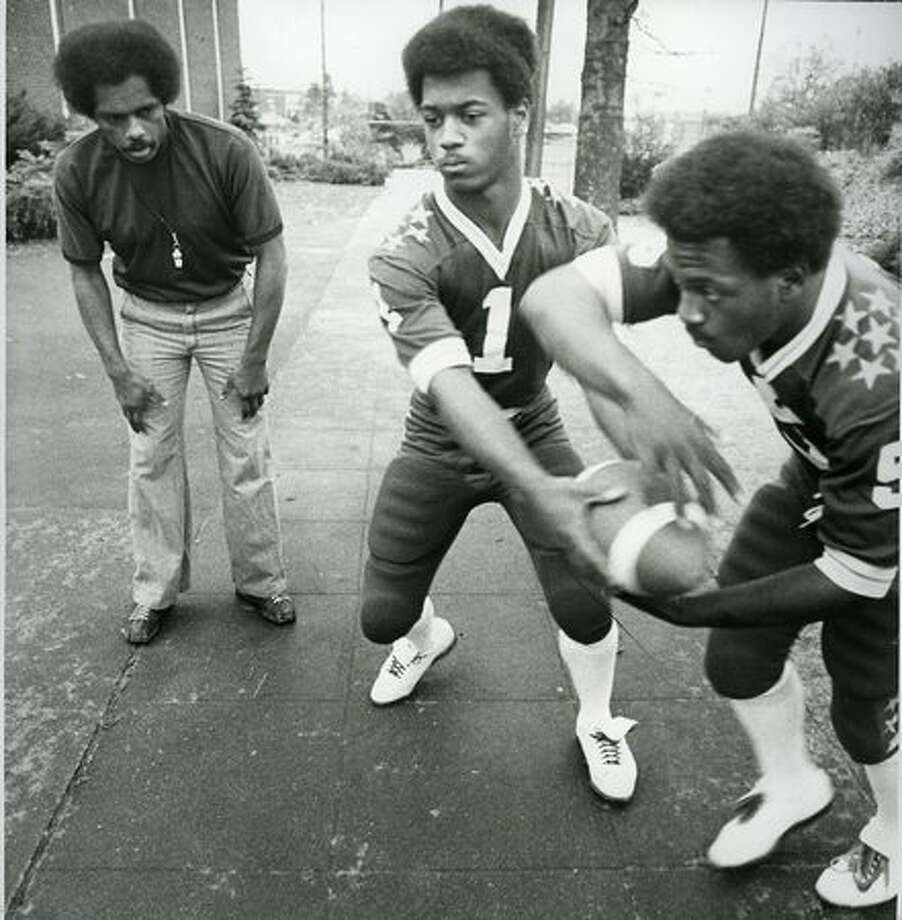 This fall 1975 photo shows Garfield football coach Al Roberts, (left) with quarter Darrell Powell and his brother Kevin Powell. Photo: P-I File