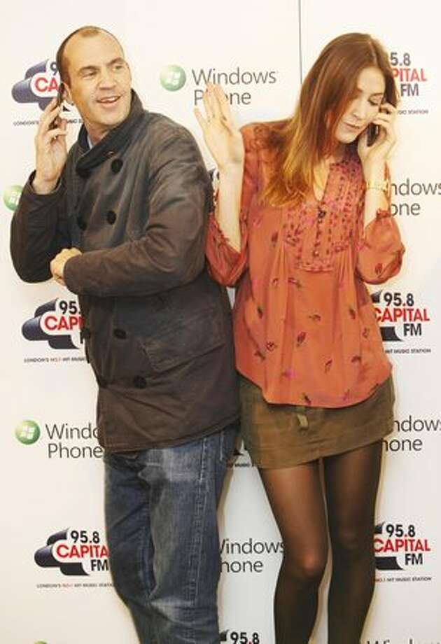 English broadcaster Johnny Vaughan and model Lisa Snowdon, from Capital FM, test out their new Windows Phone 7 devices at the Microsoft launch in the Orange Shop Oxford Street on Thursday in London. (David Parry/PA Wire) Photo: Microsoft