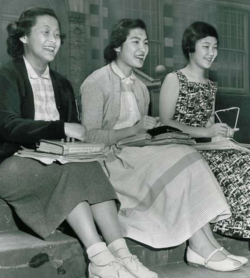 The May 1953 photo caption read: Ireme Yamauchi, Barbara Mar and May Nakamura, who tied for top scholastic honors at Garfiled High School, smile as they sit casually on the school steps. Photo: P-I File