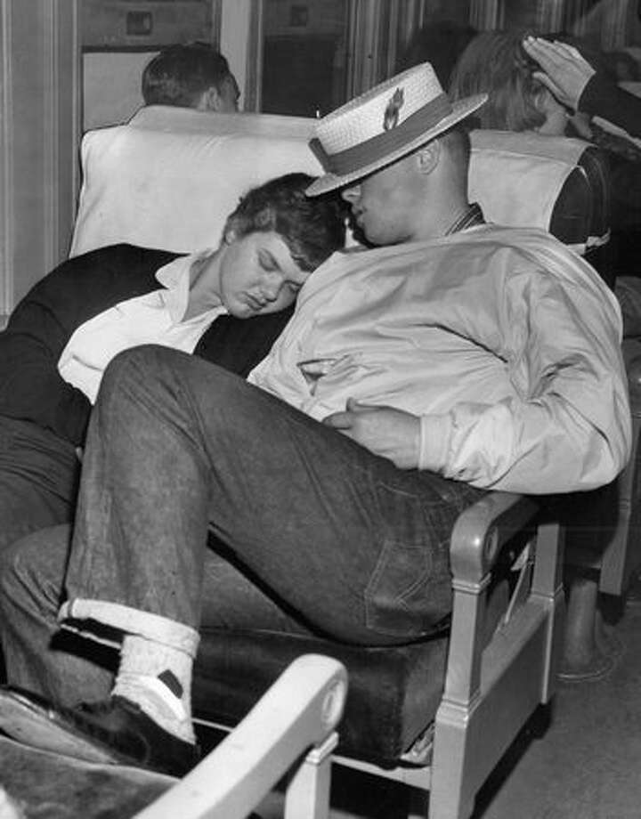 The June 1957 photo caption read: Weary Roosevelt students stretched out for some badly-needed sleep in the comfortable chair cars. Here are two tired-out passengers, Pat Carpenter and Gary Peterson, getting a little snooze before the return trip brought them back home. Photo: P-I File