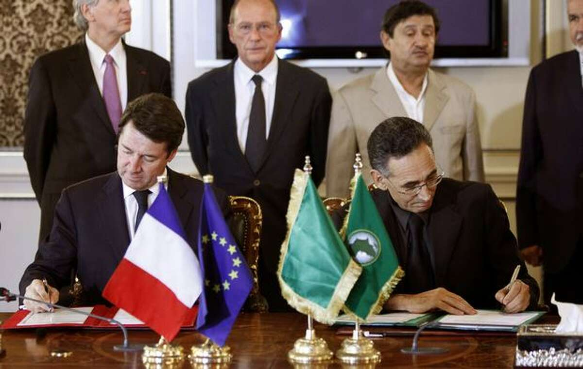 Mohammad Alahoij, Libya's minister of Economy, Trade and Investment (right), and French Industry Minister Christian Estrosi sign documents relating to delivery of a new Airbus A320 to Libyan Arab Airlines at Mitiga International Airport, in Tripoli.