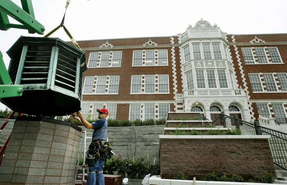 Mike Cowger of Northshore Sheet Metal, Inc. of Everett helps position an old copper exhaust vent, formerly on the roof of the school, into a place where it will serve as a lighting fixture at the newly renovated Garfield High School. September 1, 2008. Photo: P-I File
