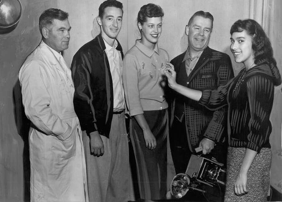 "The October 1959 photo caption read: Sandra Arino, 17, Garfield High School senior, makes with an ""okay"" sign, indicating that the school's photography class students like casual garb as modeled by some of their teachers. The teachers are (from left) John Putnam, chemistry teacher, in shop coat; Ron Patone, health and biology teacher and basketball coach; Lynne Smith, business teacher, and Joseph Marshall, photography teacher. Photo: P-I File"