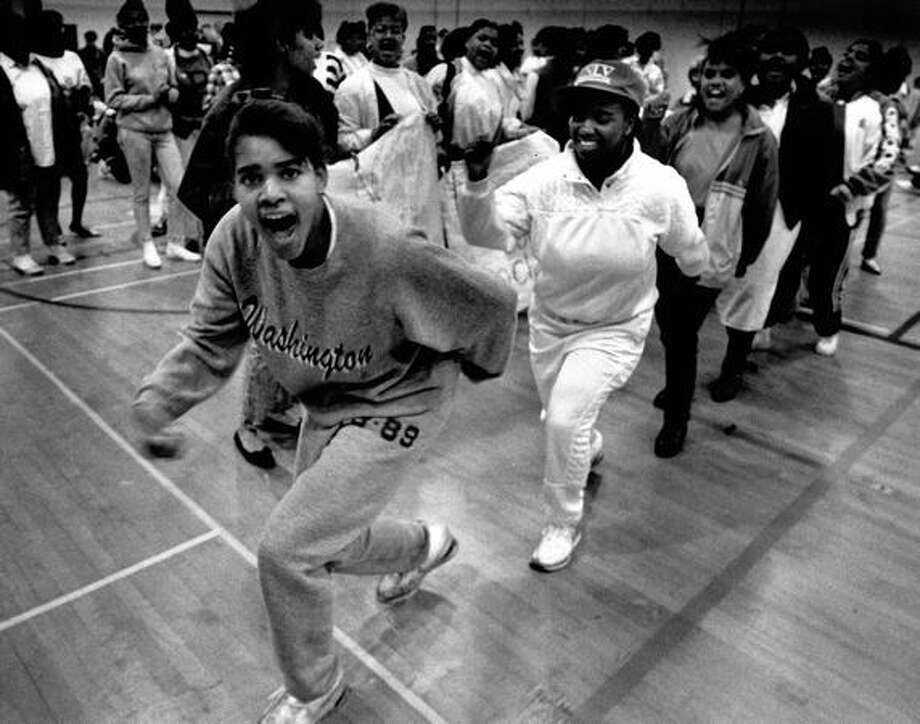 The May 1989 photo caption read: Students get into the swing of things during a protest in the Garfield High School gymnasium over plants to eliminate at least nine teaching positions. Photo: P-I File