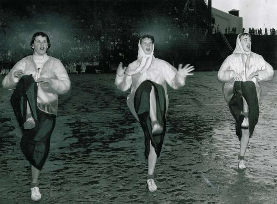 The November 1955 photo caption read: High school cheer leaders generate enthusiasm despite ocean of goon on Seattle's High School Memorial Stadium. In top photo, Garfield High School trio uncorks peppy routine, though sopping wet except for light rain jackets. Photo: P-I File