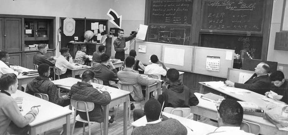 The February 1964 photo caption read: Jerry Mulder, 17, a Garfield High School junior, stands in front of his electronics class of sophomores and juniors and explains mechanical drawings (his own) on paper. Photo: P-I File