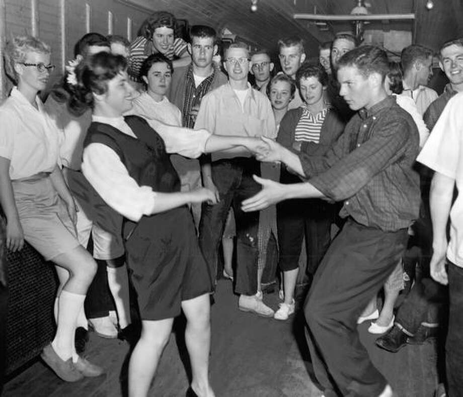 The June 1957 photo caption read: Yvonne Perier and Ben Collins, Roosevelt students, break out with some of the Elvis Presley type dancing - at least it was real fast - while a group of fellow stuents look on from the background. Photo: P-I File