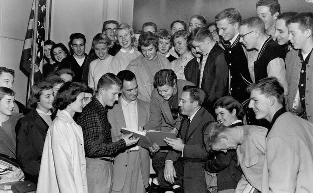 Roosevelt High School students gather around as Post-Intelligencer Ski School instructors John Prescott, Stan De Bruler and Hal Kihlman explain the program, November 30, 1955.