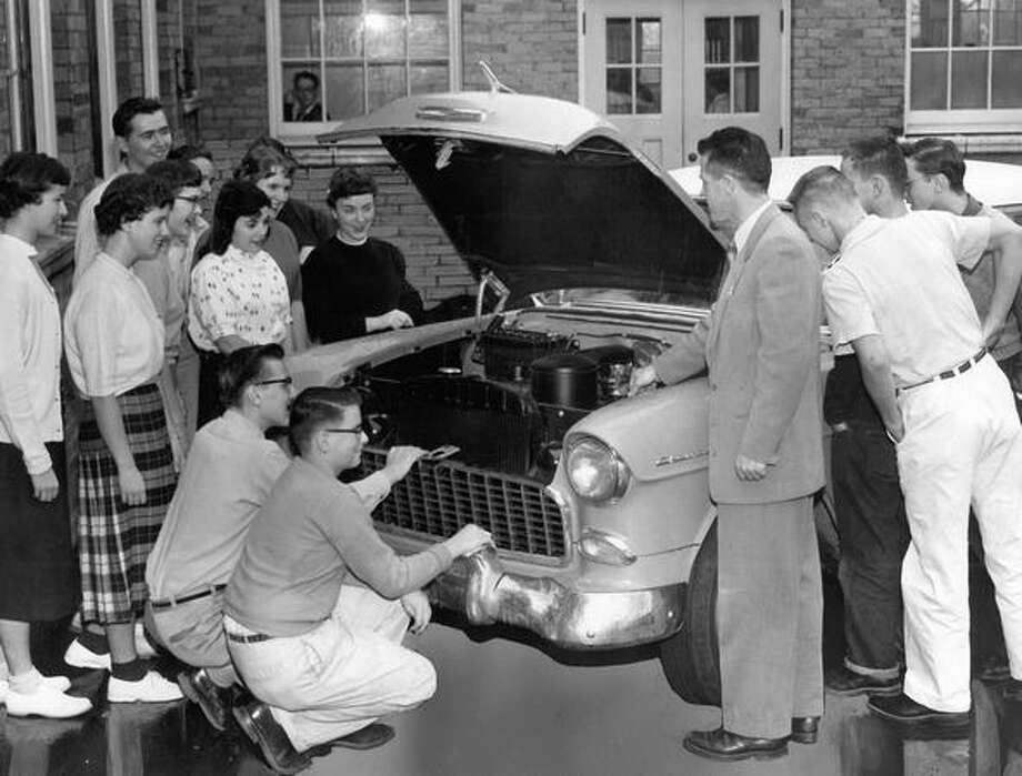 Forrest Keyes, drive-training instructor at Roosevelt High School, tells a group of students how the motor of a car works, November 1955. Photo: P-I File