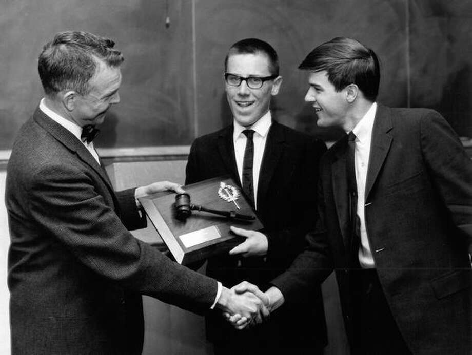 The June 3, 1966 photo caption read: Roosevelt High School of Seattle was named first place team in the state high school debate tournament held last weekend at Washington State University. At left, Dr. Arthur B. Miller, assoiate professor of speech at WSU, presents trophy to Dan McGarry, center, and Chris Murray, who formed the Roosevelt team. Photo: P-I File