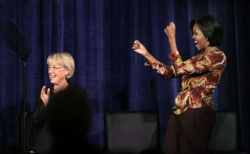 First lady Michelle Obama, right, cheers Sen. Patty Murray at a Senate campaign fundraiser in Bellevue. (AP Photo/Elaine Thompson)