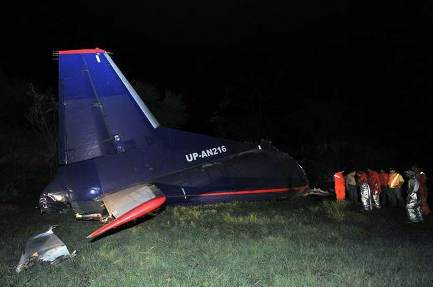 Rescuers stand next to the wreckage of an Antonov 12 cargo plane early on Thursday, April 22, 2010. The plane crashed on a rice field late Wednesday, April 21 while trying to land at nearby Clark airport in the town of Mexico, in Pampanga province, north of Manila, Philippines. Three crew members were killed. (TED ALJIBE/AFP/Getty Images)
