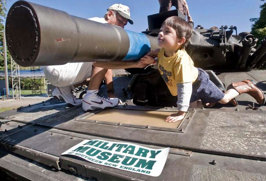Harold Bonyai of Danbury helps 4 year old Zachary Ferris of Brookfield around the gun barrel of this Sheridan tank on display at the multicultural celebration of the arts held at the Charles Ives Concert Park. The tank is from the Military Museum in Danbury. Sunday, Sept. 20, 2009 Photo: Scott Mullin / The News-Times