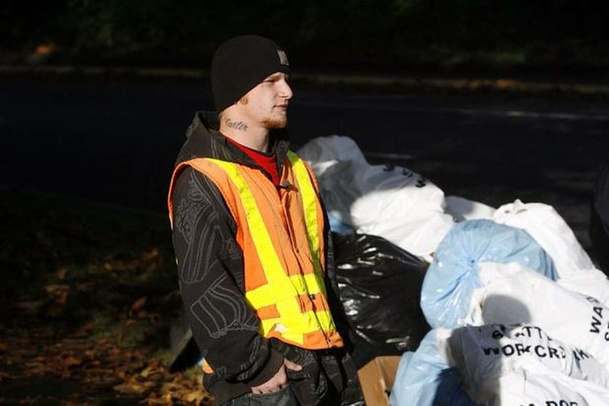 Thomas Abuhl, part of a Department of Corrections offender work crew, collects waste near South Columbian Way and South Alaska Street in Seattle. The 22-year-old, who was serving 256 hours for an assault case, said he appreciated the opportunity.