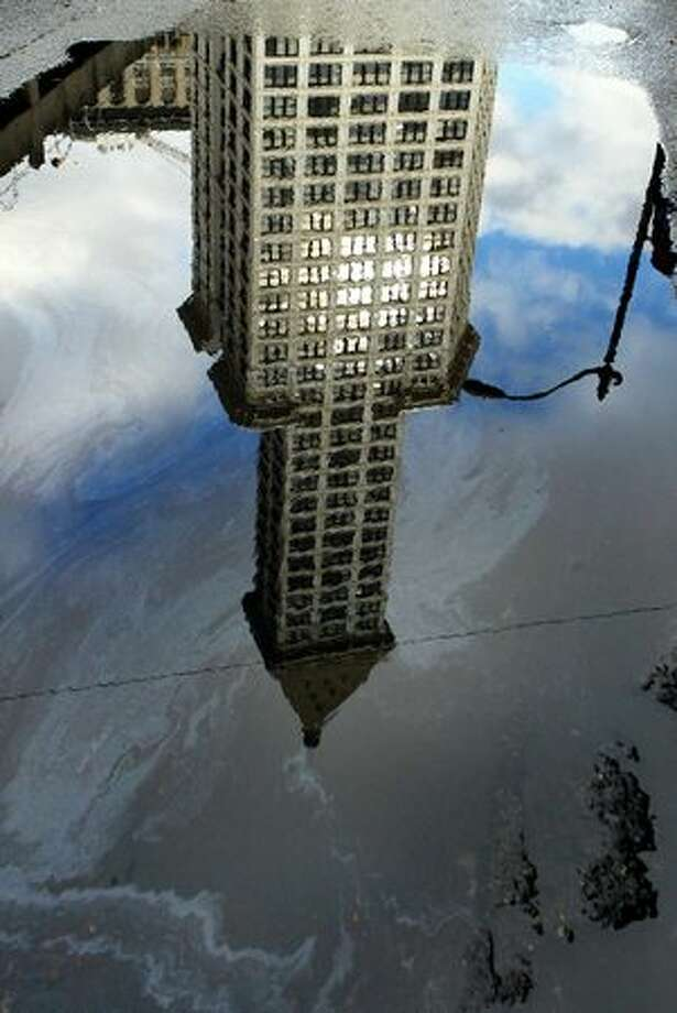 Smith Tower is reflected in a puddle on Yesler Way, 2004. Photo: P-I File / P-I File
