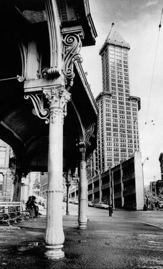 The April 1972 photo caption read: Swirl-crowned pillars from old Seattle in the Pioneer Square-Skid Road area contrast with multi-windowed Smith Tower, once the city's tallest building. Photo: P-I File / P-I File