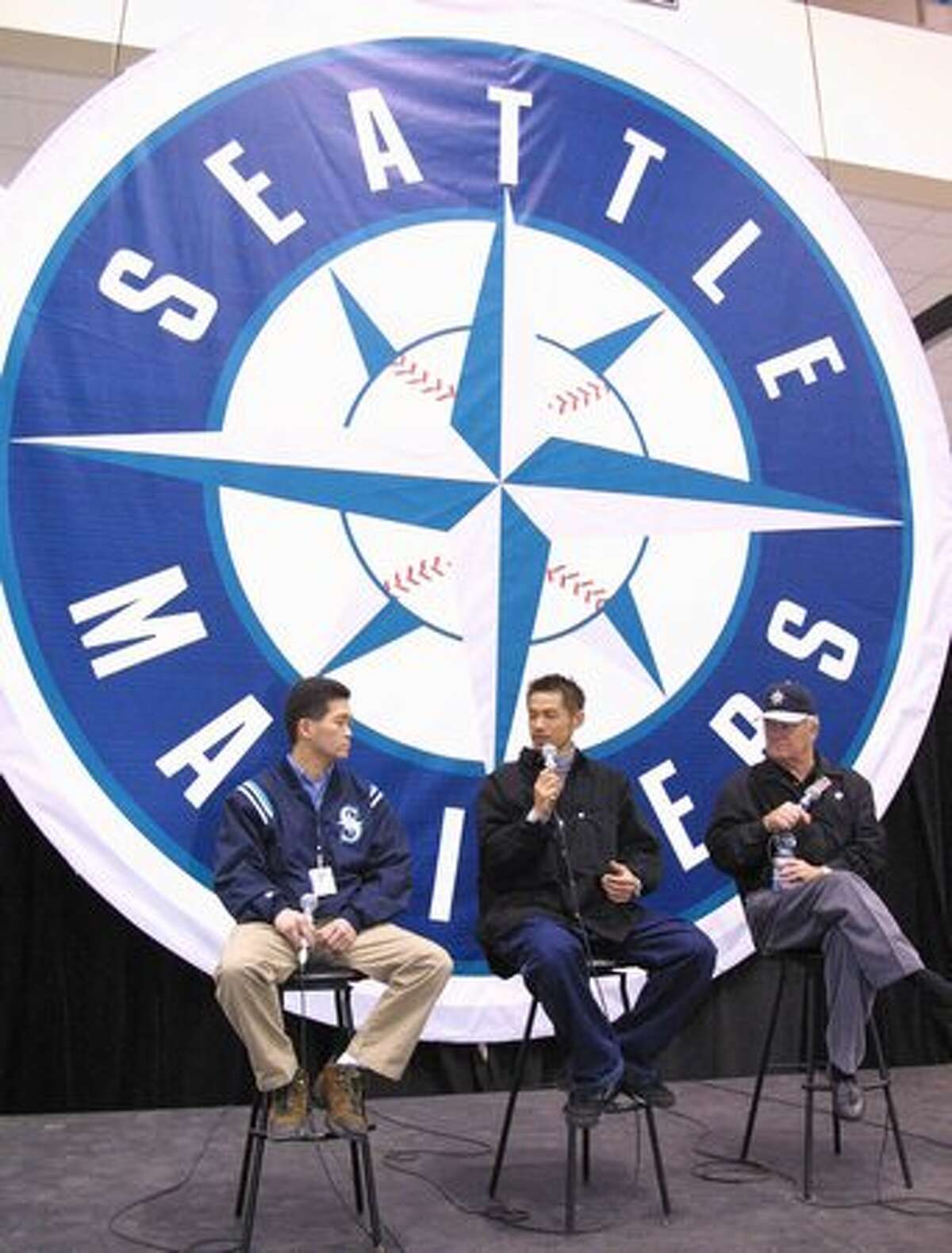 New Seattle Mariner player Ichiro Suzuki (C) answers questions from Seattle fans through team scout and translator Hide Sueyoshi (L) while team announcer Dave Niehaus looks on during a team-sponsored event on 04 February 2001.