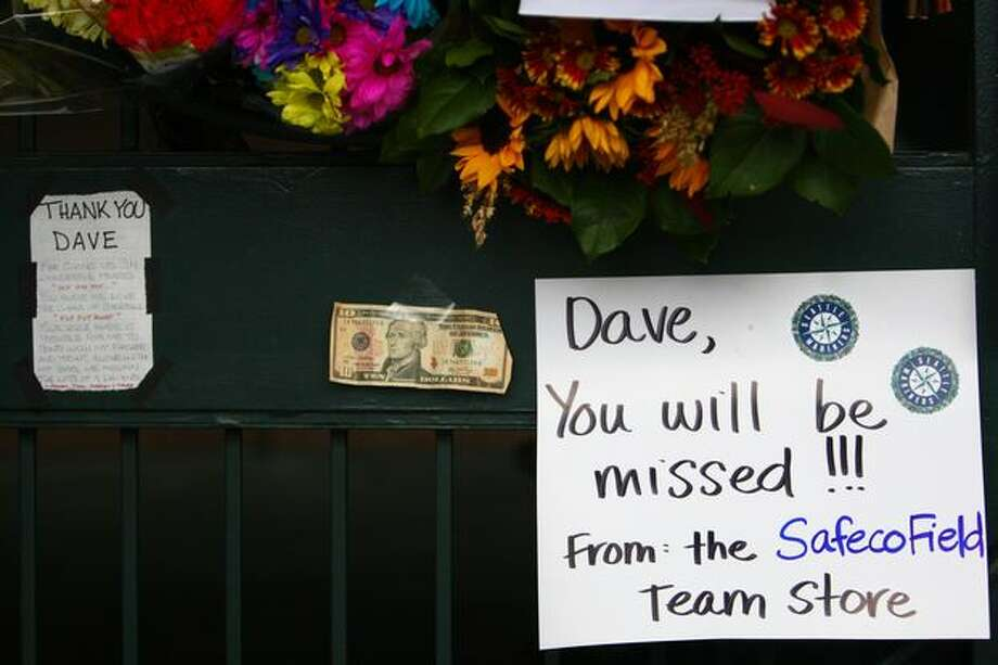 Signs, flowers and a 10 dollar bill are part of a growing memorial for longtime Mariner broadcaster Dave Niehaus at the gates of Safeco Filed on Thursday. Photo: Joshua Trujillo, Seattlepi.com / seattlepi.com
