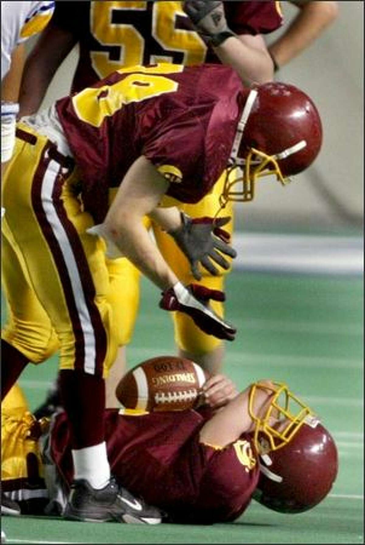 Michael Rittman looks at Joey Shanks, wondering how the O'Dea QB's elbow became stuck in his facemask.