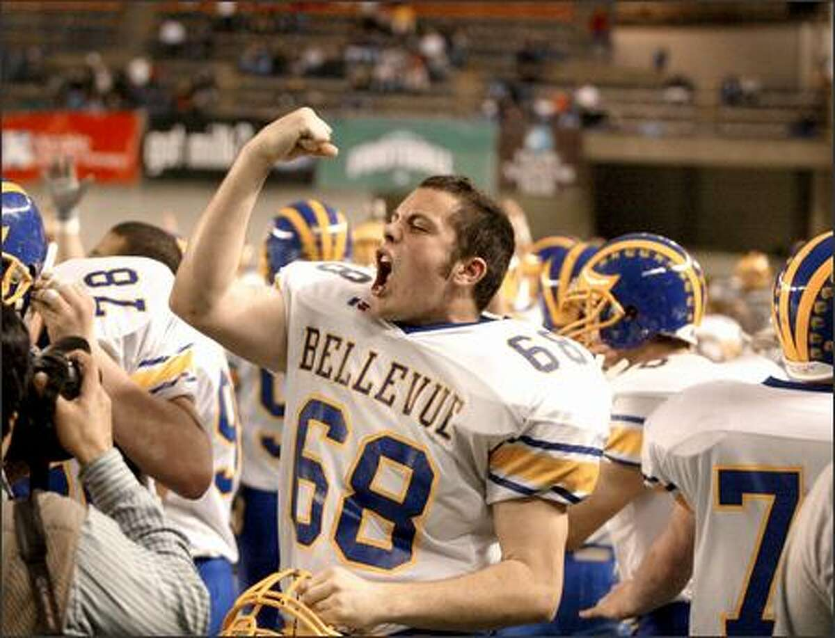 Bellevue lineman Thomas Wells, left, pumps his fist after John Coombs returned an interception 16 yards for the game-clinching touchdown with 38 seconds remaining in the game.
