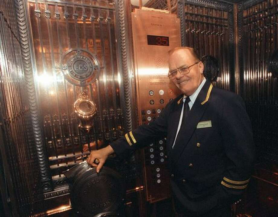The June 1999 photo caption read: Bill Bourgeois, lead elevator operator at the Smith Tower, said he enjoys working in the newly remodeled tower. Photo: P-I File / P-I File