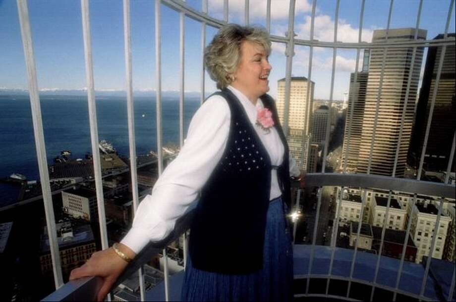 The February 1995 photo caption read: Donna Decicio, assistant manager for the Smith Tower, stands outside on the buildings observation deck and enjoys the view. The deck is open to the public and cost $2 per adult and $1 for children and seniors. Photo: P-I File / P-I File