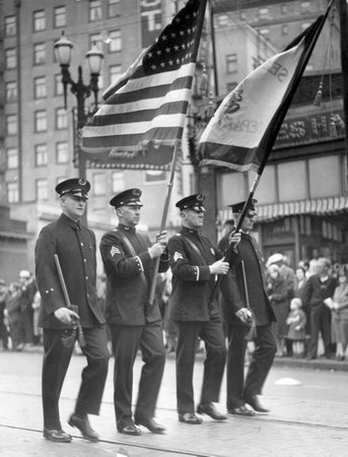 Seattle police officers hold flags during a procession. The date and location are not included with the original photo information.