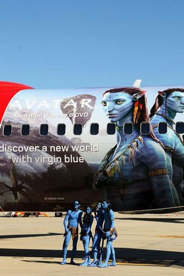 "Models dressed up as characters from the film ""Avatar"" pose in front of an Avatar-themed Virgin Blue Boeing 737 during the launch of ""Avatar"" Blu-ray and DVD at Sydney Domestic Airport, in Sydney, Australia. Photo: Getty Images"