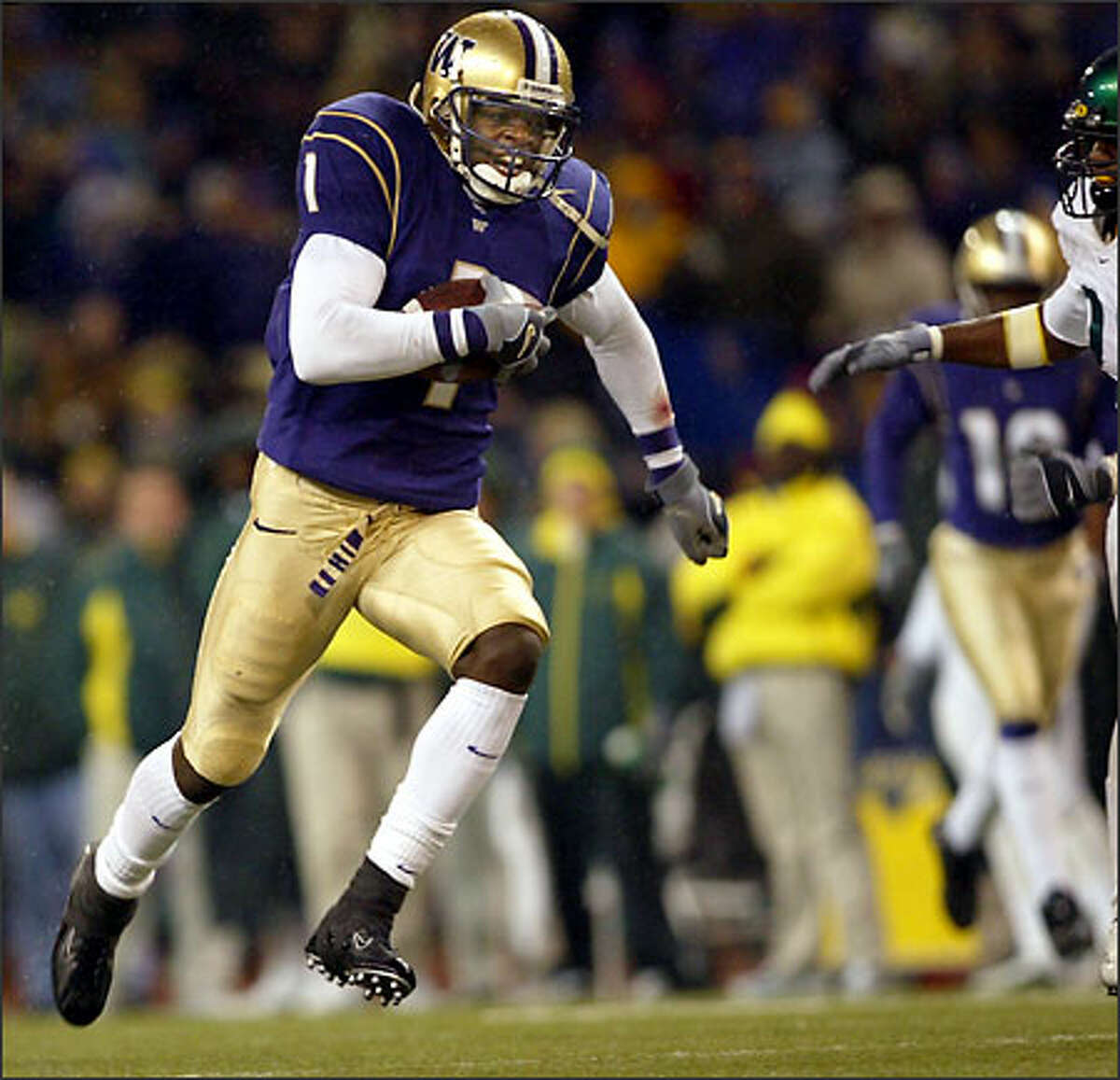 UW's Reggie Williams (1) heads down the field for a touchdown in second half.