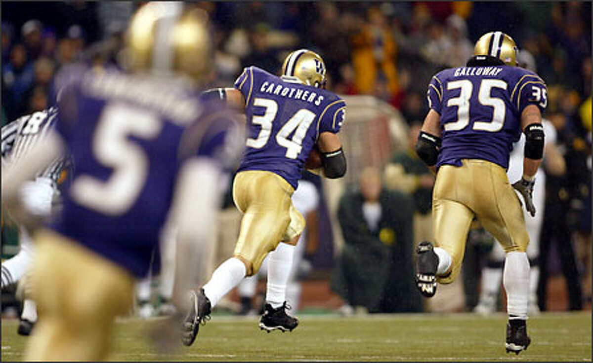 UW's Greg Carothers (34) heads towards the end zone after he recovering a ball. Tim Galloway (35), right, and Sam Cunningham (5) are in the photo.