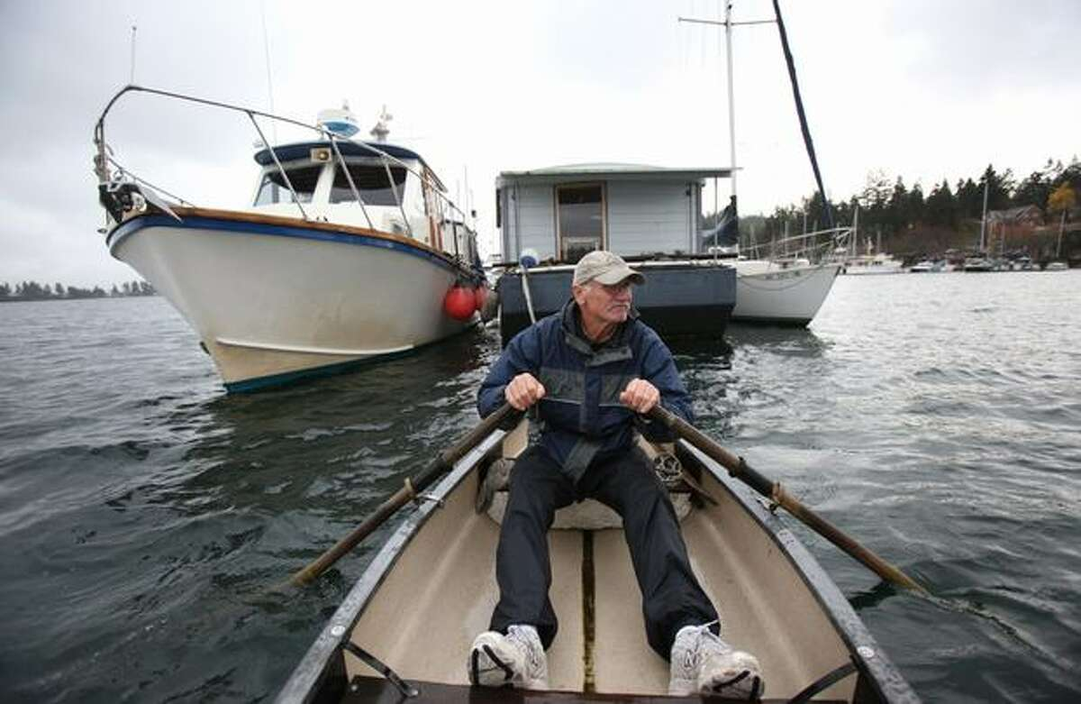 Ted Stoughton rows a skiff away from his floating home on Bainbridge Island's Eagle Harbor, Wednesday, November 17, 2010. Stoughton and other boat owners and members of the liveaboard community were served eviction notices by the Washington State Department of Natural Resources this week after plans with the Bainbridge City Council for an open-water marina were scrapped. Stoughton plans to live aboard a power boat that he recently acquired in an estate sale, shown at left. He will sell his 24-foot house barge and sail boat. Stoughton plans to hopsoctch around Puget Sound in the power boat. For decades Eagle Harbor has hosted the liveaboard community made up of an assortment of boats and house barges. The floating homes were moored on the state-managed sea floor free of charge. Stoughton has lived on the water in Eagle Harbor since 1984.