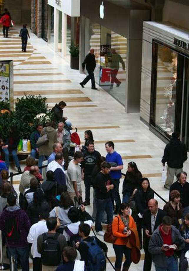 A customer walks into the nearby Apple Store as a line meanders toward the new Microsoft Store during the opening of the first local shop on Thursday at Bellevue Square mall. Photo: Joshua Trujillo, Seattle Post-Intelligencer