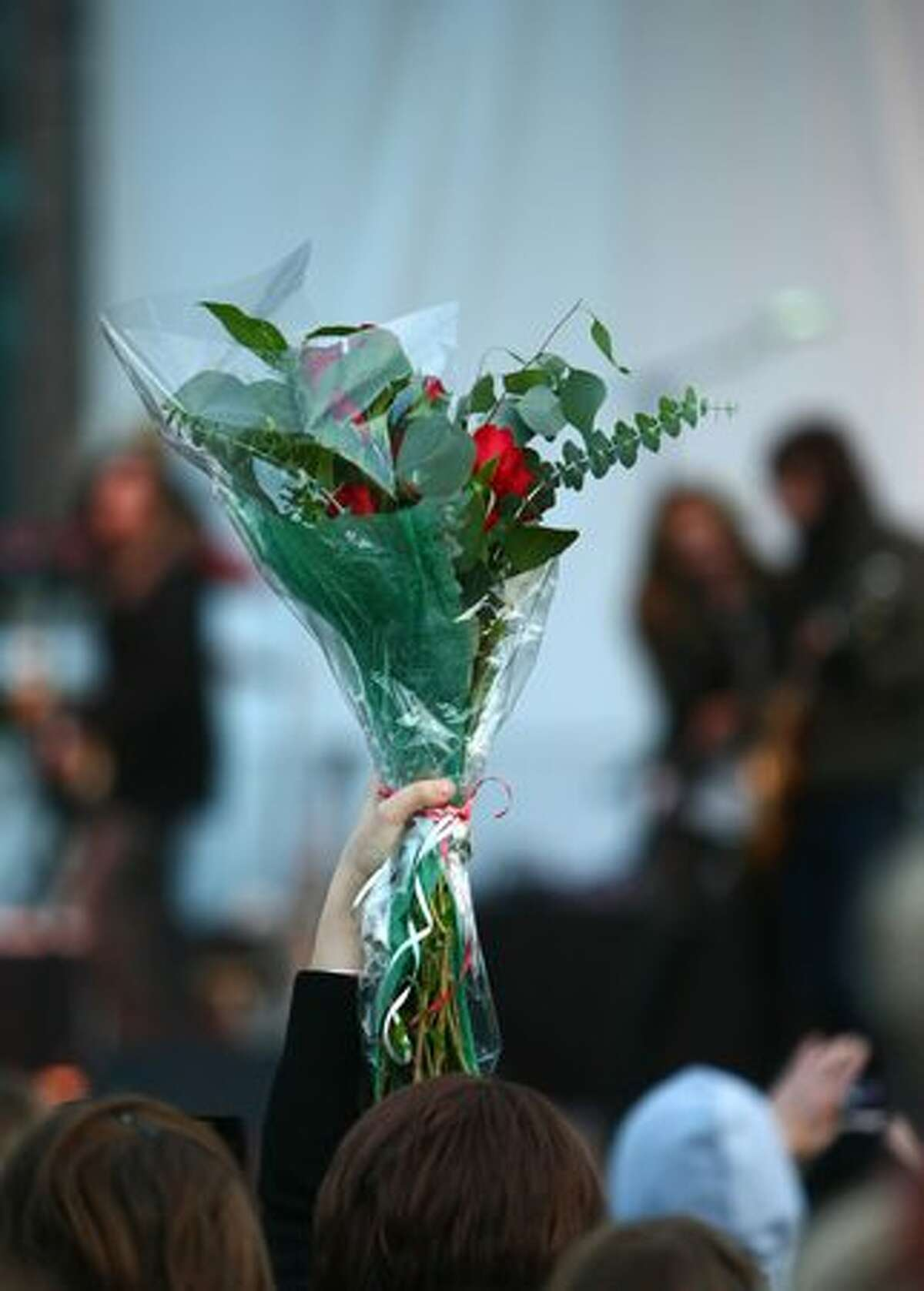 A fan raises a bouquet of roses as pop singer and actress Miley Cyrus performs in front of thousands of fans in downtown Bellevue.