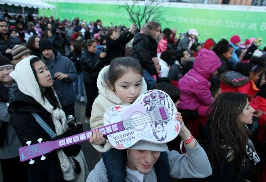 Ricky Griffiths hoists his daughter Analise, 4, and her Hannah Montana guitar as pop singer and actress Miley Cyrus performs in front of thousands of fans on Saturday in downtown Bellevue. Photo: Joshua Trujillo, Seattlepi.com