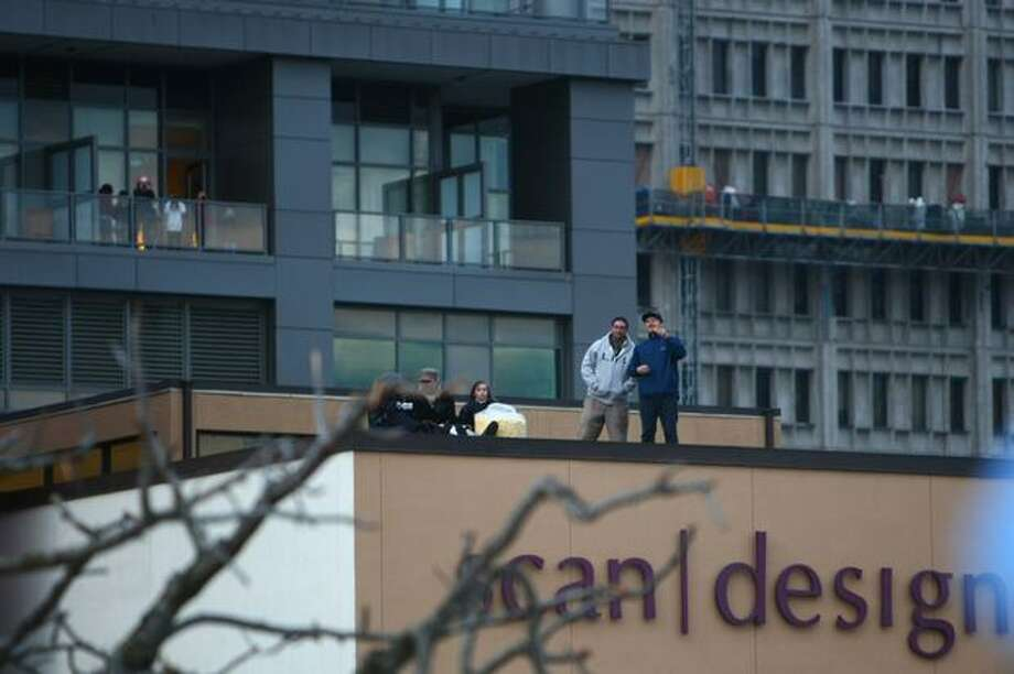 People watch from a rooftop as pop singer and actress Miley Cyrus performs. Photo: Joshua Trujillo, Seattlepi.com