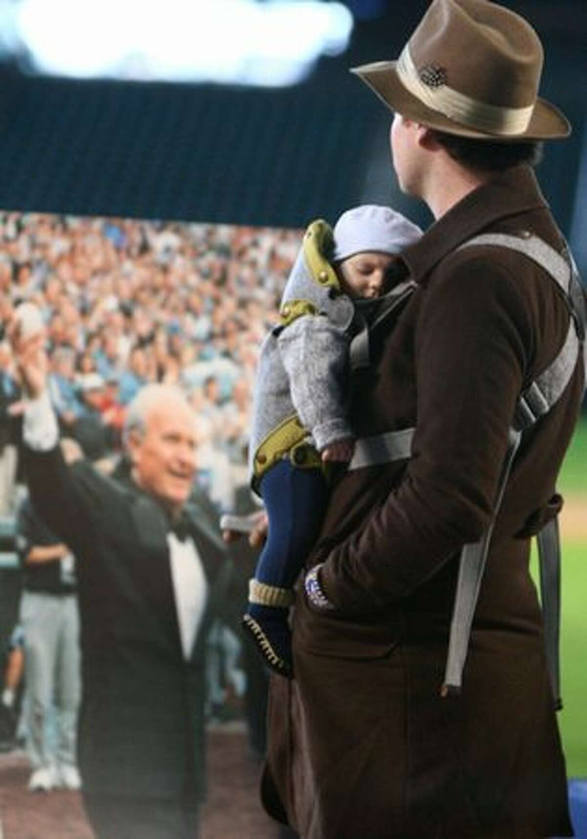 Sam Watts pays his respects with his son Easton, 3 months, during a tribute for Dave Niehaus on Saturday at Safeco Field in Seattle. Niehuas died earlier in the week from a heart attack. The popular play-by-play announcer was the voice of the Seattle Mariners since the team's inaugural season in 1977.