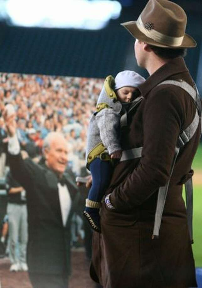 Sam Watts pays his respects with his son Easton, 3 months, during a tribute for Dave Niehaus on Saturday at Safeco Field in Seattle. Niehuas died earlier in the week from a heart attack. The popular play-by-play announcer was the voice of the Seattle Mariners since the team's inaugural season in 1977. Photo: Joshua Trujillo, Seattlepi.com