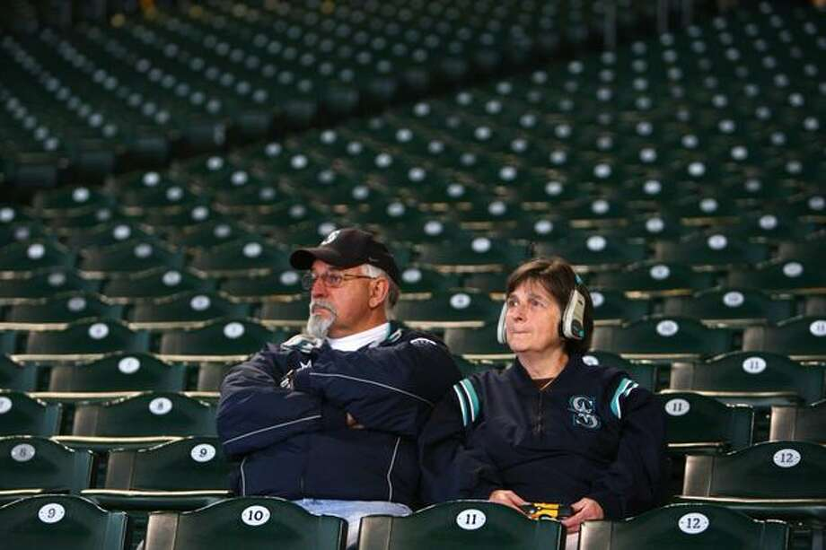 Bill and Karen Garner of Silverdale listen to a re-broadcast of the 1995 American League Division Series game against the New York Yankees during a tribute for Dave Niehaus on Saturday at Safeco Field in Seattle. Niehuas died earlier in the week from a heart attack. The popular play-by-play announcer was the voice of the Seattle Mariners since the team's inaugural season in 1977. Photo: Joshua Trujillo, Seattlepi.com