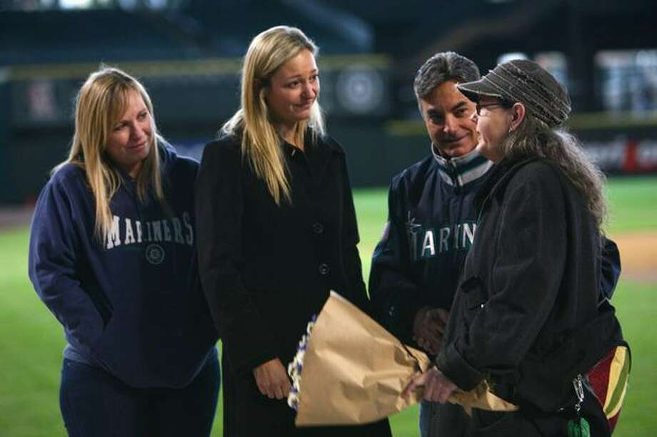 A fan pays her respects to play-by-play announcer Rick Rizzs, second from right, and Dave Niehaus' daughter Greta Niehaus Dunn, center, during a tribute for Niehaus on Saturday at Safeco Field in Seattle. Niehuas died earlier in the week from a heart attack. The popular play-by-play announcer was the voice of the Seattle Mariners since the team's inaugural season in 1977. Photo: Joshua Trujillo, Seattlepi.com