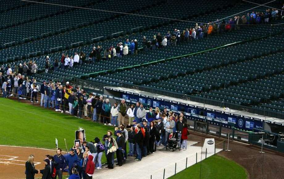 Seattle Mariners fans wait in line to greet the family and friends of Mariners broadcaster Dave Niehaus during a tribute to the voice of the Mariners on Saturday at Safeco Field in Seattle. Over 3,500 fans waited in line to pay tribute to Niehuas, who died earlier in the week from a heart attack. The popular play-by-play announcer was the voice of the MBL team since the team's inaugural season in 1977. Photo: Joshua Trujillo, Seattlepi.com