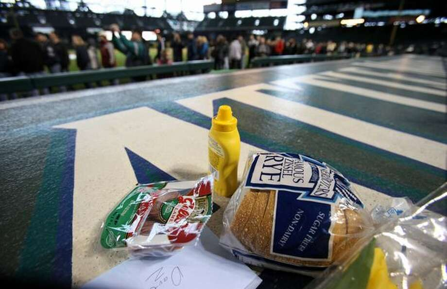 Rye bread, mustard and salami rest on the top of the Mariners' dugout during a tribute for Dave Niehaus on Saturday at Safeco Field in Seattle. The items were part of his repertoire of catchy sayings. Niehuas died earlier in the week from a heart attack. The popular play-by-play announcer was the voice of the Seattle Mariners since the team's inaugural season in 1977. Photo: Joshua Trujillo, Seattlepi.com