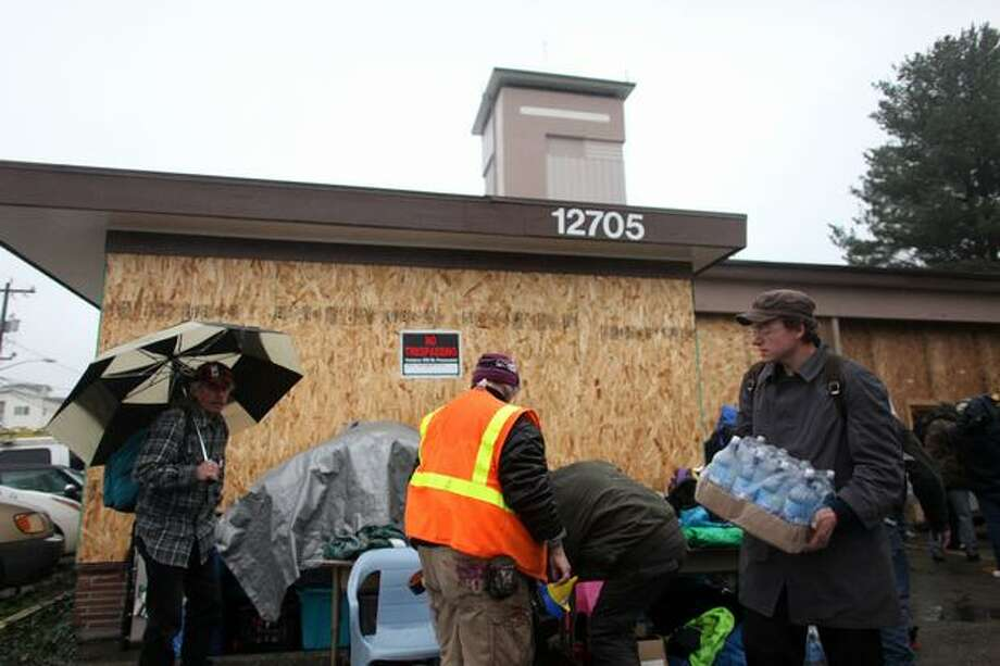 "People organize supplies as ""Nickelsville"" homeless camp residents relocate to Seattle Fire Department's former Station 39 building on Monday, November 15, 2010. The homeless camp, named as a jab at former Seattle Mayor Greg Nickels, relocated to the neighborhood after a stint in the University District. No notice was given to neighbors that the camp was moving there, upsetting some Lake City residents. Photo: Joshua Trujillo, Seattlepi.com"